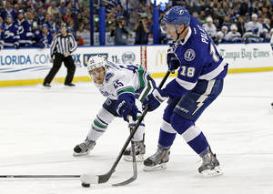 Photo - Tampa Bay Lightning left wing Ondrej Palat (18), of the Czech Republic, shoots and scores a goal around Vancouver Canucks center Jordan Schroeder (45) during the second period of an NHL hockey game Monday, March 17, 2014, in Tampa, Fla. (AP Photo/Brian Blanco)