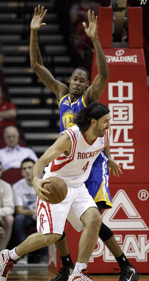 Photo -   Houston Rockets' Luis Scola (4) drives around Golden State Warriors' Mickell Gladness (32) during the first quarter of an NBA basketball game Saturday, April 21, 2012, in Houston. (AP Photo/David J. Phillip)