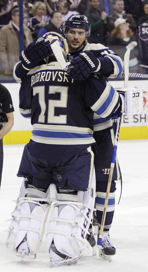 Photo - Columbus Blue Jackets' Artem Anisimov, right, of Russia, congratulates Sergei Bobrovsky, also of Russia, on his shout out against the Carolina Hurricanes after an NHL hockey game on Friday, Jan. 10, 2014, in Columbus, Ohio. The Blue Jackets won 23-0. (AP Photo/Jay LaPrete)