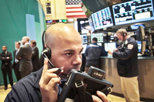 Photo - Fred DeMarco, a trader with Bay Crest Partners, talks into a headset during early trading Tuesday at New York Stock Exchange. AP Photo