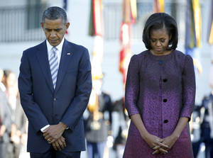 Photo -   President Barack Obama and first lady Michelle Obama, joined by members of the White House staff pause during a moment of silence to mark the 11th anniversary of the Sept, 11th, Tuesday, Sept. 11, 2012, on the South Lawn of the White House in Washington. (AP Photo/Carolyn Kaster)