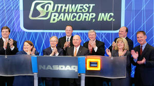 Photo - Chairman of the Board Russell Teubner, third from left, and President and CEO Mark Funke, sitting next to Teubner, are shown with Southwest Bancorp?s executive team in New York on March 11. <strong>Zef Nikolla</strong>