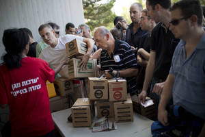 Photo - Israelis line up at a gas mask distribution center in Tel Aviv, Israel, Wednesday, Aug. 28, 2013. Large crowds of Israelis have lined up at gas-mask distribution centers across the country in anticipation of a possible Syrian attack on Israel. (AP Photo/Oded Balilty)