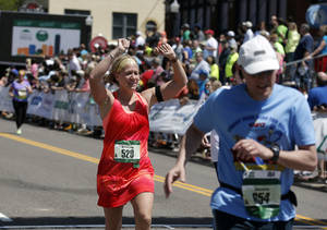 Photo - Chrissie Boatman of Tecumseh, Okla., cheers as she finishes the Marathon during the 14th Annual Oklahoma City Memorial Marathon in Oklahoma City, Sunday, April 27, 2014. Photo by Sarah Phipps, The Oklahoman
