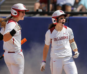 Photo - OU's Callie Parsons, right, is congratulated by teammate Javen Henson after Parsons beat the throw at home plate and scored an in-the-park home run in the bottom of the sixth inning to put the Sooners'  ahead 3-1in their  win by the same score over the Ragin' Cajuns of University of Louisiana-Lafayette in the first of two games the Sooners played on Saturday, May 31, 2014, in the Women's College World Series at ASA Hall of Fame Stadium. #19 for Louisiana-Lafayette is Shelbi Redfearn.    Photo by Jim Beckel, The Oklahoman