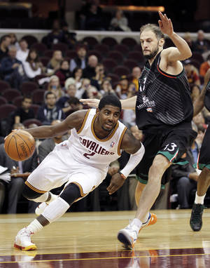 Photo -   Cleveland Cavaliers' Kyrie Irving (2) drives past Montepaschi Siena's Victor Sanikidze (13) in the second quarter of a preseason NBA basketball game, Monday, Oct. 8, 2012, in Cleveland. (AP Photo/Tony Dejak)