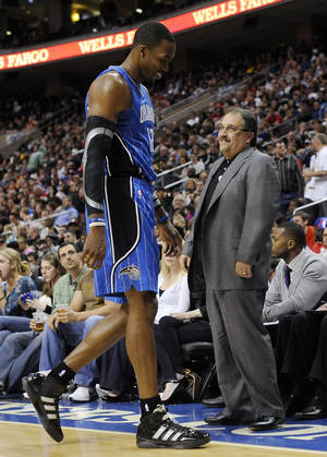 Photo -   Orlando Magic coach Stan Van Gundy, right, and Dwight Howard smile at each other as Howard comes off the floor in the first half of an NBA basketball game against the Philadelphia 76ers, Saturday, April 7, 2012, in Philadelphia. (AP Photo/Michael Perez)