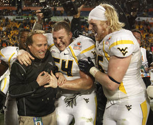 photo - West Virginia Mountaineers linebacker Hunter Bittner (54) and offensive linesman Pat Eger (76) hug head coach Dana Holgorsen, left, after defeating Clemson 70-33 at the Orange Bowl NCAA college football game Thursday, Jan. 5, 2012, in Miami . (AP Photo/Lynne Sladky) ORG XMIT: SLS129