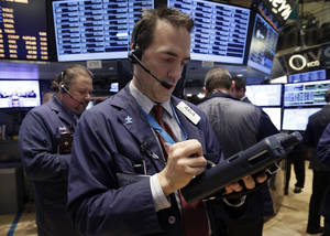 Photo - Trader Gregory Rowe, center, works on the floor of the New York Stock Exchange, Thursday, Dec. 19, 2013. Stocks edged lower in early trading Thursday, pulling back from record levels. (AP Photo/Richard Drew)
