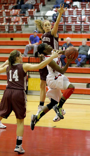 photo - Del City's Dionna Collins shoots a layup between Edmond Memorial's Jessica Fostet (14) and Jenny Roy (24) during the girls high school basketball game between Del City and Edmond Memorial at Del City High School,  Tuesday,Jan. 8, 2013. Photo by Sarah Phipps, The Oklahoman