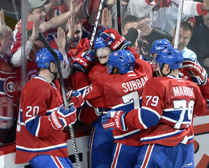 Photo - Montreal Canadiens left wing Max Pacioretty (67) is mobbed by teammates after scoring the winning goal against the Tampa Bay Lightning during third period National Hockey League Stanley Cup playoff action on Tuesday, April 22, 2014 in Montreal. (AP Photo/The Canadian Press, Ryan Remiorz)