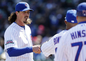 Photo - Chicago Cubs starter Jeff Samardzija, left, talks to Emilio Bonifacio as he walks walks back to the dugout during the third inning of a baseball game against the Philadelphia Phillies in Chicago, Saturday, April 5, 2014. (AP Photo/Nam Y. Huh)