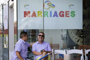 Photo - Jose Guerrero, left, and Patrick Rodriguez chat before their wedding ceremony in West Hollywood, Calif., Monday, July 1, 2013.  The city of West Hollywood is offering civil marriage ceremonies for same-sex couples free of charge Monday. (AP Photo/Jae C. Hong)
