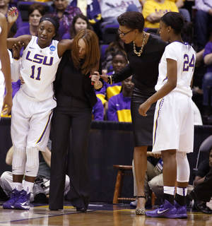 Photo - In a March 23, 2014 photograph, LSU guard Raigyne Moncrief (11) is helped off the floor by a trainer after injuring her left knee, as basketball coach Nikki Caldwell, right, and teammate DaShawn Harden (24) check on her in the second half of an NCAA college basketball first-round tournament game against Georgia Tech in Baton Rouge, La. LSU officials said Moncrief was to be examined by doctors Monday and her playing status would be determined prior to the start of the second round game Tuesday night. (AP Photo/Rogelio V. Solis)