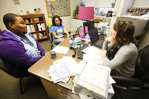 photo - Northwest Classen seniors DeShawn Holliday, left, and Gabriella Rowles talk Thursday with school  counselor Ashley Westerman.  Photo by Steve Gooch, The Oklahoman