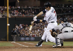 photo -   Minnesota Twins' Joe Mauer hits an RBI single in the seventh inning of a baseball game, as the Twins came from behind to beat the New York Yankees 5-4 in a baseball game Tuesday, Sept. 25, 2012 in Minneapolis. At right is Yankees catcher Russell Martin who had a solo home run in the game. (AP Photo/Jim Mone)
