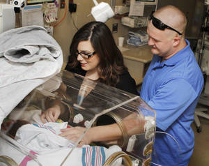 photo - Roseanna and Chance McCall touch their baby girl Addyson Grace. Photos by Paul Hellstern, The Oklahoman