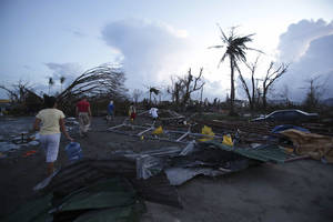 "Photo - Residents walk by debris after powerful Typhoon Haiyan slammed into Tacloban city, Leyte province, central Philippines on Saturday, Nov. 9, 2013. The central Philippine city of Tacloban was in ruins Saturday, a day after being ravaged by one of the strongest typhoons on record, as horrified residents spoke of storm surges as high as trees and authorities said they were expecting a ""very high number of fatalities."" (AP Photo/Aaron Favila)"