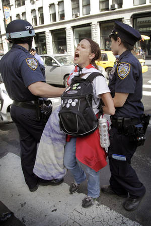 photo -   Police take Amanda Lodoza, an activist associated with the Occupy Wall Street movement, into custody during a march in New York, Sunday, Sept. 16, 2012. The Occupy Wall Street movement will mark its first anniversary on Monday. (AP Photo/Seth Wenig)
