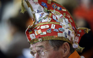 Photo - A Dutch skating fan, his hat filled with Olympic pins, watches the women's 1,000-meter speedskating race at the Adler Arena Skating Center during the 2014 Winter Olympics in Sochi, Russia, Thursday, Feb. 13, 2014. (AP Photo/David J. Phillip )