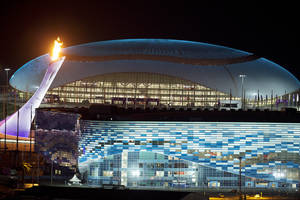 Photo - The Olympic Cauldron, left, is lit during a test between the Bolshoy Ice Dome, top, and the Iceberg Skating Palace, foreground, early Thursday morning, Feb. 6, 2014, in Sochi, Russia, prior to the start of the 2014 Winter Olympics. (AP Photo/Pavel Golovkin)