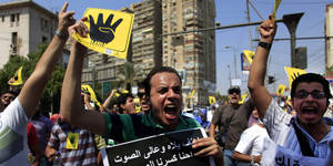 "Photo - Supporters of Egypt's ousted President Mohammed Morsi chant slogans and hold placards showing an open palm with four raised fingers, which has become a symbol of the Rabaah al-Adawiya mosque, where Morsi supporters had held a sit-in for weeks that was violently dispersed on Aug. during a protest in Cairo, Egypt, Friday, Sept. 6, 2013. Thousands of protesters flowed out of mosques on Friday in Muslim Brotherhood-led rallies against the military-backed government a day after a car bomb in the Egyptian  capital marked a substantial escalation in EgyptÂ's violent turmoil. Arabic writing on the black poster reads "" Chant loud we Brooke the voice with death.""(AP Photo/Khalil Hamra)"