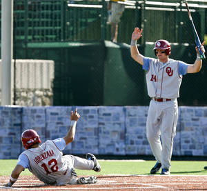 Photo - Oklahoma's Hector Lorenzana (12) slides safely into home and is met by teammate Matt Oberste (14) during an NCAA college baseball tournament regional game against Connecticut at English Field in Blacksburg, Va., Saturday, June 1, 2013. (AP Photo/Michael Shroyer) ORG XMIT: VAMS143