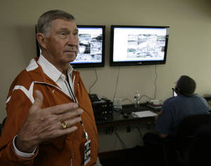 Photo - In this photo taken Saturday, Oct. 10, 2009, University of Texas athletics director DeLoss Dodds, foreground, explains the workings of the stadium security video monitor area before a Longhorns NCAA college football game in Austin, Texas. In the background, officer W.R. Pieper views a myriad of camera angles around the stadium.  (AP Photo/Harry Cabluck)