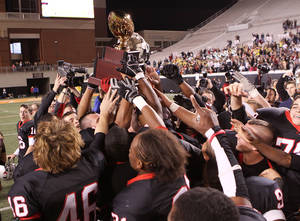 Photo - CLASS 6A HIGH SCHOOL FOOTBALL STATE CHAMPIONSHIP GAME / TULSA UNION / TROPHY: Union hoists the gold ball in the air after winning the state championship during the 6A State Championship game between Jenks and Union at OSU on December 3, 2010.  JOEY JOHNSON/For the Tulsa World