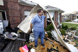"Photo - Randy McKeever, removes part of what he believes is his neighbors garage door from the front of his tornado damaged home Wednesday, April 4, 2012, in Forney, Texas. The mayor of Forney, Texas, says it's ""a real blessing"" that nobody was killed in the community by the tornadoes that ripped through parts of the Dallas area yesterday.  (AP Photo/Tony Gutierrez) ORG XMIT: TXTG110"