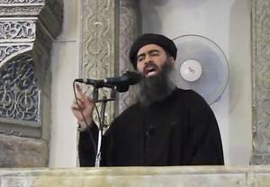 Photo - This image made from video posted on a militant website Saturday, July 5, 2014, which has been authenticated based on its contents and other AP reporting, purports to show the leader of the Islamic State group, Abu Bakr al-Baghdadi, delivering a sermon at a mosque in Iraq. A video posted online Saturday purports to show the leader of the Islamic State extremist group that has overrun much of Syria and Iraq delivering a sermon at a mosque in Iraq, in what would be a rare - if not the first - public appearance by the shadowy militant. (AP Photo/Militant video)