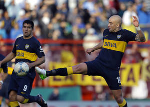 Photo -   Boca Juniors' Santiago Silva, right, kicks the ball while playing against Argentinos Juniors during an Argentina's league soccer match in Buenos Aires, Argentina, Sunday, Sept. 9, 2012. (AP Photo/Eduardo Di Baia)