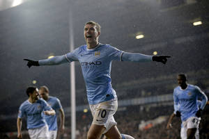 Photo - Manchester City's Edin Dzeko celebrates scoring his side's third goal during the English Premier League soccer match between Tottenham Hotspur and Manchester City at White Hart Lane stadium in London, Wednesday, Jan. 29, 2014.  (AP Photo/Matt Dunham)