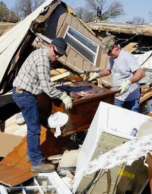 Photo - Roger Jones, right, gets help searching the debris of his mobile home from his nephew Josh Jones, left, on Newport Road in Lone Grove Wednesday, Feb. 11, 2009. BY PAUL B. SOUTHERLAND, THE OKLAHOMAN