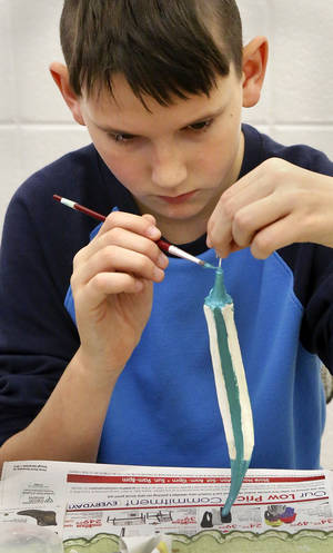 photo - Draper Goostree, 11, of Mustang, paints an ornament to take home or hang on a Christmas tree at Will Rogers Garden Exhibition Center.