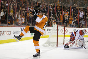 Photo - Philadelphia Flyers' Matt Read, left, celebrates after scoring against Washington Capitals' Braden Holtby during the second period of an NHL hockey game, Tuesday, Dec. 17, 2013, in Philadelphia. (AP Photo/Matt Slocum)