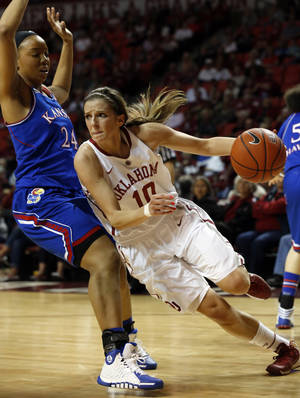Photo - OU's Morgan Hook, right, drives past Kansas' CeCe Harper during the Sooners' win on Saturday. Hook scored 15 points in the win. Photo by Steve Sisney, The Oklahoman