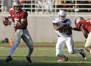 Photo - Florida State quarterback Jameis Winston (5) makes a cut to avoid a sack by North Carolina State defensive end Mike Rose (90) in the second quarter of an NCAA college football game on Saturday, Oct. 26, 2013, in Tallahassee, Fla. (AP Photo/Phil Sears)