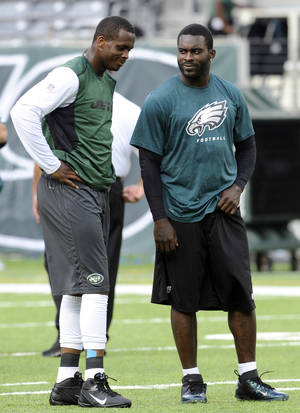 Photo - FILE - In this Aug. 29, 2013, file photo, New York Jets quarterback Geno Smith, left, talks to Philadelphia Eagles quarterback Michael Vick before a preseason NFL football game in East Rutherford, N.J. The Jets signed the former Philadelphia Eagles quarterback to a one-year deal Friday, March 21, 2014, and released Mark Sanchez, the one-time face of the franchise.   (AP Photo/Bill Kostroun, File)