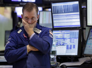 photo - In this Thursday, Jan. 10, 2013, photo, specialist Edward Zelles works on the floor of the New York Stock Exchange. Wall Street futures were mostly flat in world markets prior to the opening bell Friday Jan. 11, 2013. (AP Photo/Richard Drew)