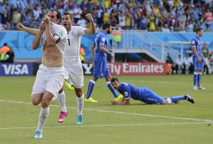 Photo - Uruguay's Diego Godin, left, celebrates after scoring his side's first goal during the group D World Cup soccer match between Italy and Uruguay at the Arena das Dunas in Natal, Brazil, Tuesday, June 24, 2014. (AP Photo/Petr David Josek)