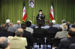 "Photo - In this picture released by an official website of the office of the Iranian supreme leader, Supreme Leader Ayatollah Ali Khamenei, speaks to a group of officials and scientists of the Atomic Energy Organization of Iran in Tehran, Iran, Wednesday, April 9, 2014. Iran's Supreme Leader urged Iran's negotiators Wednesday not to give in to ""coercive words"" from world powers at talks over Tehran's nuclear program. Iran is celebrating its National Nuclear Technology Day as talks with world powers over its contested program continue in Vienna. A Portrait of the late revolutionary founder Ayatollah Khomeini hangs in background.(AP Photo/Office of the Iranian Supreme Leader)"