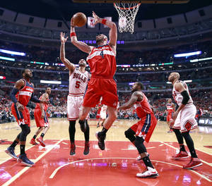 Photo - Washington Wizards center Marcin Gortat (4) grabs a rebound over Chicago Bulls forward Carlos Boozer (5) during the first half of Game 2 in an opening-round NBA basketball playoff series game Tuesday, April 22, 2014, in Chicago. Also watches on the play are John Wall (2), Trevor Booker (35) and Taj Gibson (22). (AP Photo/Charles Rex Arbogast)