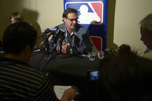 Photo - Los Angeles Dodgers manager Don Mattingly, center, takes a question from reporters during a media availability at baseball's winter meetings in Lake Buena Vista, Fla., Tuesday, Dec. 10, 2013.(AP Photo/Phelan M. Ebenhack)