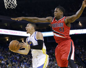 Photo - Golden State Warriors' Stephen Curry (30) drives past Portland Trail Blazers' Thomas Robinson (41) during the second half of an NBA basketball game on Sunday, Jan. 26, 2014, in Oakland, Calif. Golden State won 103-88. (AP Photo/Marcio Jose Sanchez)