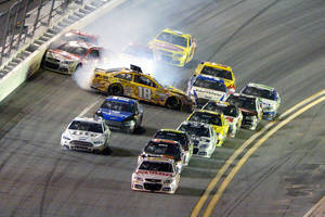 Photo - Dale Earnhardt Jr., front, leads the racers to the finish line as Kyle Busch (18) starts a collision coming out of Turn 4 during the NASCAR Daytona 500 auto race at Daytona International Speedway in Daytona Beach, Fla., Sunday, Feb. 23, 2014. (AP Photo/Phelan M. Ebenhack)
