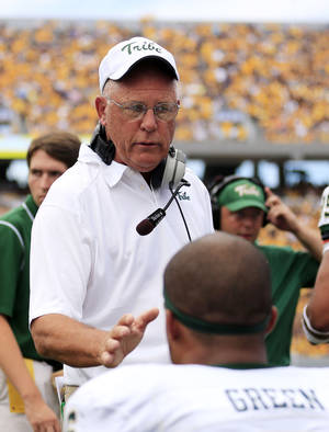 Photo - William and Mary coach Jimmye Laycock speaks with Airek Green (6) on the sidelines during the second quarter of their NCAA college football game against West Virginia in Morgantown, W.Va., on Saturday, Aug. 31, 2013. (AP Photo/Christopher Jackson)