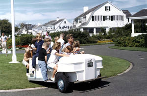 Photo - In this Sept. 3, 1962 photo provided by the John F. Kennedy Library and Museum, President Kennedy drives his nieces and nephews in golf cart at the family home in Hyannis Port, Mass. The JFK Library opened a special exhibit Friday, June 27, 2014, featuring some never-before displayed artifacts from the Kennedy family's summers on Cape Cod, including the golf cart. (AP Photo/White House via the John F. Kennedy Library and Museum in Boston, Robert Knudsen)