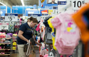 Photo - In this June 5, 2014 photo, Mary Bullen, merchandise supervisor of the infant and girls section, makes price changes to clothing at the Wal-Mart Supercenter in Rogers, Ark. Wal-Mart Stores Inc. reports quarterly financial results after the market closes on Thursday, Aug. 14, 2014. (AP Photo/Sarah Bentham)