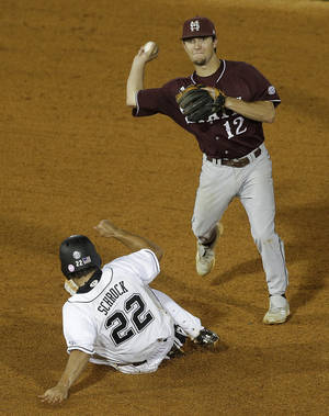 Photo - Mississippi State shortstop Adam Frazier (12) turns a double play in the sixth inning as South Carolina's Max Schrock (22) tries to break up the play in their Southeastern Conference Tournament college baseball game at the Hoover Met in Hoover, Ala., Wednesday, May 22, 2013. (AP Photo/Dave Martin)